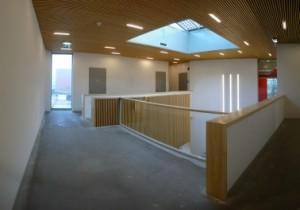 De dubbelhoge hal gezien vanaf de eerste verdieping. In het daklicht zijn PV cellen opgenomen
