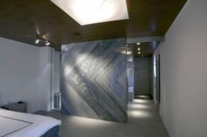 Master bedroom annex badkamer in de kelder, sober strak wit met natuurstenen schijfvormig element als ruimtescheiding