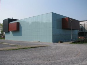 Het gebouw is een glazen doos met drie uitgebouwde dozen