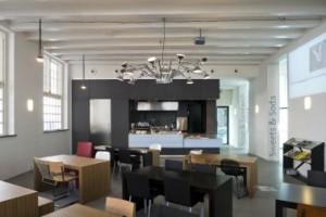 Sandberg café in de oudbouw, met een variëteit aan stoelen: moderne klassiekers van onder andere Rietveld en Mart Stam, en nieuwere designstoelen van Maarten van Severen