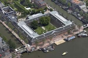 Luchtfoto met op voorgrond de Amstel, duidelijk zichtbaar zijn de glazen daken van de tentoonstellingszalen en het auditorium