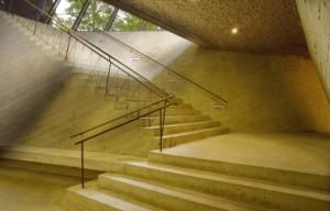 De trap van okerkleurig beton heeft op de verticale vlakken een nerfstructuur en is op de horizontale vlakken gestraald