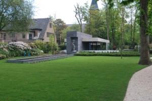 De tuin met rechts het meanderende pad vanaf het bestaande woonhuis