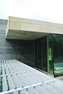 De hoofdingang met op de voorgrond een van de drie daklichten met als zonwering kantelbare lamellen voorzien van een print