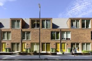 3 Smalle woningen. Het metselwerk van dikformaat baksteen in wildverband is doorgezet in de dakkapellen en in de tuinmuurtjes
