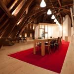 De lichte berkentriplex plint en vloer contrasteren met de monumentale donkere houten kapconstructie