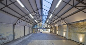 Negen stalen dakspanten overspannen de enorme ruimte, waarin sporen van het garageverleden overal zichtbaar zijn. Een lichtstraat op het noorden loopt over de hele lengte van het dak