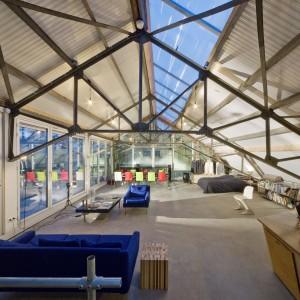 De eerste verdieping in het glazen huis is één grote ruimte. Wonen, werken en ontspannen gaan hier hand in hand gaan. De industriële designinrichting versterkt de garagesfeer.
