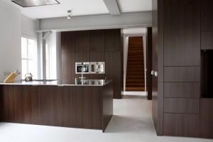 Een halfhoog voorzieningenblok aan de woonkamerkant vormt het keukeneiland. In het hoge blok erachter is alle keukenapparatuur weggewerkt.