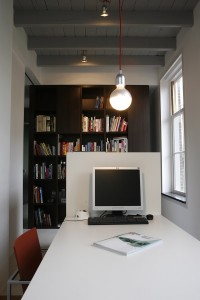 Achter de keuken ligt de spreekkamer van Dyckhoffs bureau Flow Architecten. Het hoge voorzieningenblok dat beide ruimtes scheidt heeft een open kastenwand in de spreekkamer. 'Voor meer privacy kan de opening tussen blok en buitenmuur met glas worden dichtgemaakt, maar dat vonden wij niet nodig.' De witte tafel is onderdeel van een roomdivider met opbergvakken aan de smalle zijden. Ook hier lampen van DAB, herkenbaar aan de rode draad.
