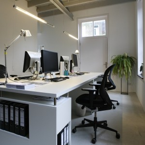 Een groot bureau in het kantoor van Flow Architecten biedt ruimte aan vier werkplekken. Bureaulampen van Artemide en twee tl-buizen met zichtbare mechaniek zorgen voor verlichting.