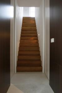 De eiken trap naar de zolderverdieping verdeelt de achterkant van het huis in kantoor en spreekkamer. 'De trap is geïnspireerd op een minimalistisch ontwerp van de Britse architect John Pawson. Ik ben een groot bewonderaar van zijn werk.' In een afgesloten ruimte onder de trap staan server en kopieerapparaat.