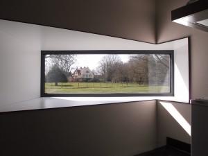 Uitstekend venster in een van de lage vleugels is gericht op het neorenaissance landhuis uit 1905.