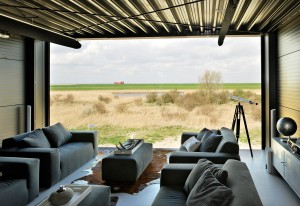 De glaspartij op de tweede bouwlaag biedt een magnifiek uitzicht over de polder. Vergelijk dat eens met het huis pal naast woonhuis Ripken. Foto: Lars Courage