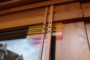 Dunne verticale latjes voor de pui verzachten de overgang. Strookjes oranje perspex die op deze latjes zijn bevestigd dienen hetzelfde doel en vangen en kleuren het licht. Foto: Jacqueline Knudsen