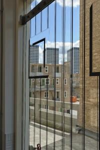 Op de glazen deuren van de nieuwe trappenhuizen is een print aangebracht van de oude houten toegangsdeuren. Foto: Bas Kooij