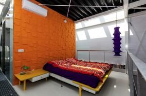 Slaapkamer op de tweede verdieping, met een vide boven de woonkamer. Links een gangpad van roosters. 13 dakramen zorgen voor lichtinval van bovenaf.