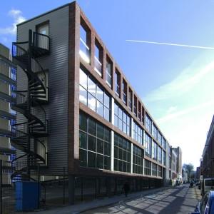 Bedrijfsruimte en woning aan de Boogaardsstraat in Rotterdam. Dit gebouw kenmerkt zich door het overbouwen van een bestaande straat en parkeerterrein. Hierdoor lijkt het boven het maaiveld te zweven. Op de bovenste verdieping bevindt zich een bedrijfswoning. Wat het gebouw uniek maakt is de 54 meter lange glasgevel waarachter zich een dynamisch kantoor bevindt welke slechts vijf meter diep is. Hiermee maakt het gebouw de straat in een keer af. Foto: Edwin Prins