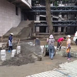 In China werken veel vrouwen in de bouw, hier bestraten ze de ruimte bij een gloednieuw appartementencomplex in Guiyang. Wolbert zit in de architectenselectie voor de restyling van het belendende hotel in neoklassieke stijl, dat aan dit complex gekoppeld wordt.