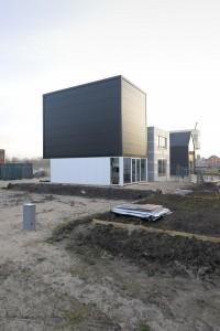 Van buiten is Licht Budget in Almere een zwarte doos zonder gevelopeningen op een witte plint op een krappe kavel. Van binnen dringt het daglicht tot diep de woning binnen door de openingen aan drie kanten van het dakvlak. Foto: Lars Courage