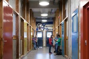 De eigen kleuren van het schoonbeton en het Amerikaans grenenhout zijn overal in het gebouw zoveel mogelijk hersteld. Deuren, kunstwerken én leerlingen zorgen voor kleur. Foto: Raoul Suermondt