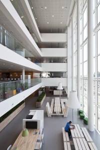 Rond het atrium liggen open verdiepingen met naast flexplekken vele loungezitjes, royale fauteuils en picknicktafels met grote schemerlampen. Foto: Raoul Suermondt