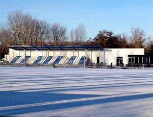 Voor voetbalvereniging Neptunus-Schiebroek heeft LG architecten een clubgebouw geïntegreerd in een bouwdeel met de tribune. In plaats van het standaard plaatmateriaal als achterwand van de tribune bevinden zich er verticale planken van lariks hout.