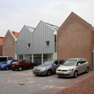 Verbindende collectieve woonkamer tussen twee bouwstroken ter afscherming van de binnenhofjes.