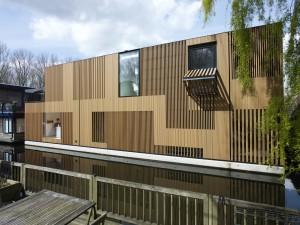 Watervilla nabij het Olympisch stadion in Amsterdam, ontwerp Framework Architecten & Studio Prototype. Het contact tussen water en woning staat centraal in het ontwerp. De verticale lattenstructuur in de gevels zorgt voor de gewenste privacy, maar ook voor een subtiel lichtspel in de woning zelf. Foto: Jeroen Musch
