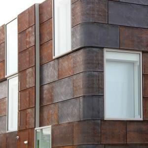 De cortenstalen panelen zijn op de hoeken rond gezet, waardoor het gebouw een zachtere uitstraling krijgt. Foto: Bas Boerman