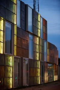 Om de Domus 's nachts vindbaar te maken, zijn verticale strips met gekleurde led-lampjes in de spouw aangebracht. Als de verlichting na zonsondergang aangaat, worden oneffenheden in de folie als een levende huid door de perforatie zichtbaar. Foto: Bas Boerman