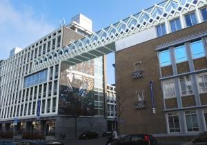 Uitvergroot over de volle hoogte van een verdieping ontstaat een sierlijke vakwerkconstructie die vloeiend van 'daklijst' van het monumentale Oogziekenhuis na een overspanning van 14 meter overgaat in de zakelijke gevel van het Ooghuis (het voormalig gewestelijk arbeidsbureau uit 1964). Groeneveld: 'Na de prijsvraag is het plan uitgewerkt tot VO en er is al overlegd met welstand. Het Oogziekenhuis is voornemens de brug in de toekomst te realiseren.'