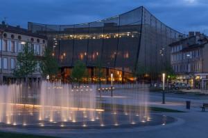 Theater in Albi, ontwerp architect Dominique Perrault.  Aan de zijde van het plein doet de gewelfde gebouwschil denken aan een open toneelgordijn.