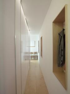 3.Vanaf de entree loopt een gang van 80 cm breed naar de voorkant van de woning. Rechts zijn op drie plekken nissen aangebracht om de lange wand te breken en het ruimtegevoel te vergroten. Berging, wc, douche en kledingkast zitten verborgen achter een wand van lichtdoorlatend polycarbonaat. De lichtlijn achter de deuren verlicht ook de gang.