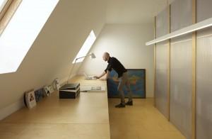 6.In de werkkamer staan drie multiplex werkbladen op schragen tegen het dakbeschot. 'Het achterliggende idee is, dat de vloer doorloopt en als het ware tegen de muur omklapt,' legt Dooghe uit. In een dichtgemaakte opening naar de gang maakte Dooghe een opbergnis voor ordners. De achterwand van de boekenkast tussen werkkamer en keuken gebruikt hij als projectbord. De twee lichtbakken van Philips zijn precies even breed als de kast.