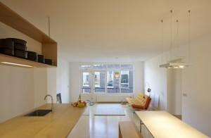 8.Dooghe: 'Multiplex verbindt alles in huis. Het ligt op de vloer en ook keuken, banken en zijkanten van kasten en nissen zijn ervan gemaakt. Het is een mooi en makkelijk te verwerken materiaal, dat met een laag vernis goed tegen water kan.' Het keukenblok is efficiënt ingericht met greeploze Ikea kastjes aan de eetkamerkant en koelkast, afwasmachine en schuifkasten aan de kookkant. De hangende bovenkast is voor de ene helft open servieskast en voor de andere helft voorraadkast en behuizing van de afzuigkap. De inrichting is rustig en open gehouden. De rechthoekige lamp boven de eettafel is een Grand Prix van Delta Light. In de woonkamer staan een Artifort bank van Kho Liang Ie en een schommelstoel van Charles Eames. De vintage vloerlamp vond Dooghe in een vorige woning en de lamp boven het vloerkleed is een ontwerp van Philippe Starck.