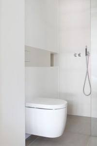 De twee badkamers in het huis van Marike Andeweg zijn ontworpen door Studiodoccia. De Push, een geïntegreerde keramische drukplaat met gelaserde knoppen zorgt ervoor dat de drukplaat mooi overloopt in de nis van de douche.