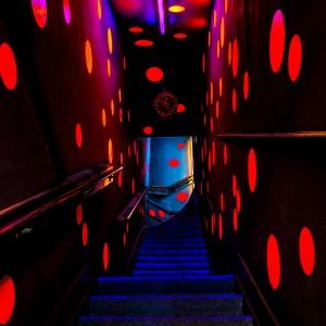5. Via een dubbele watervaltrap met zwarte wanden en plafond, waarop roze ballen oplichten in het blacklight – een kunstwerk van VollaersZwart – bereik je de tweede verdieping van een 19e eeuws pand met twee woningen boven elkaar. Foto Jonathan Collingridge