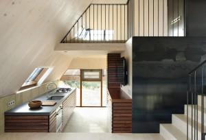 De gewalste staalplaten waarmee het rookkanaal van de haard bekleed is, geven het huis iets ruigs.