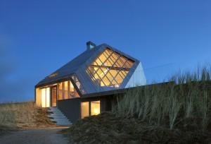 Vanuit het noordwesten, grote vensters zorgen voor een intense beleving van duinen en zee. De gevel met de lichte helling vormt als vanzelf de loungebank op het terras