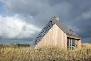 Vanuit het zuidwesten, het sculpturale bouwwerk is van top tot teen bekleed met hout en heeft vanuit elk standpunt weer een ander silhouet