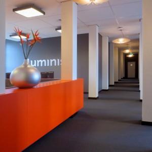 De houten lamp is een ontwerp van Luminis-medewerker Pien ter Voorde. Het heldere licht trekt de bezoekers door het midden van de loft naar de gang.