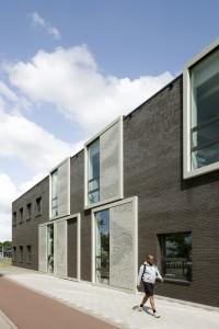 Verrijdbare deuren van oude fabrieksloodsen in de omgeving stonden model voor de verschuifbare zonneschermen van geperforeerde aluminium panelen.