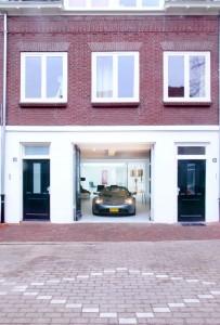 Via de originele werkplaatsdeuren kan de Tesla naar binnen. Rechts de voordeur van de garageloft en links de toegang tot de bovenwoning.