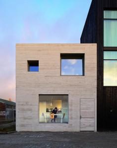 Het Deventer Havenkwartier is een nieuwe zelfbouwwijk in het voormalige havengebied van de Hanzestad. Tussen oude loodsen en particuliere woonhuizen staat het eerste nieuwbouwhuis van architect Marieke Kums. De gevel, inclusief de voordeur, is van ruw beton gemaakt. Raamkozijnen en een dakrand ontbreken.