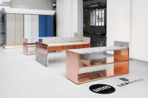 Lensvelt presenteert stoere bureaublokken UNM van marmer en koper, ontwerp: Nina Graziosi. Achteraan zijn gebruikte archiefkasten geplaatst in een sierlijke omlijsting van hout en piepschuim naar ontwerp van Edward van Vliet.
