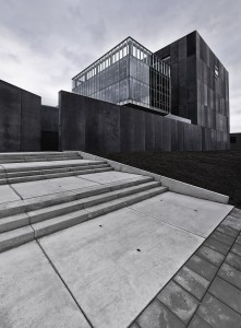 De creatieve afdelingen in glazen dozen worden omkaderd door een gebouwdelen in zwart beton met parkeren, kantoren en ondersteunende diensten.