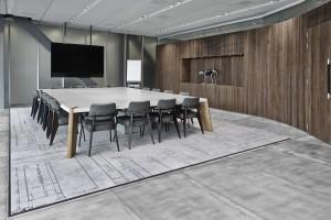 Vergaderzaal met meubilair van Prouvé en print van constructietekening op het vloerkleed