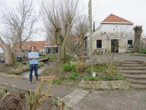 Jamie van Lede in de tuin achter de koestal (geheel rechts). Rechts achter hem de serre van zijn woning. Daarachter een andere stal van de voormalige boerenhofstede. Op het eilandje, dat via twee bruggetjes bereikbaar is vanuit zijn tuin, heeft hij een moestuin.