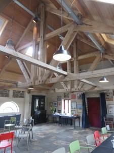 De zaal met verhoogde kap en verlaagde vloer, met hergebruik van oude spanten en tegels en klinkers. Boven de stalvensters is de oorspronkelijke hoogte zichtbaar